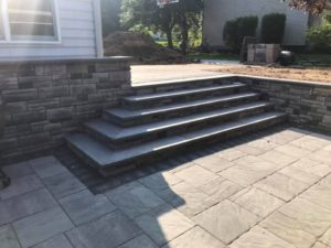 raised patio and steps in Langhorne using Ep Henry's beautiful cast stone wall Adirondack color and game changing Bristol stone pavers pewter blend with color tech.