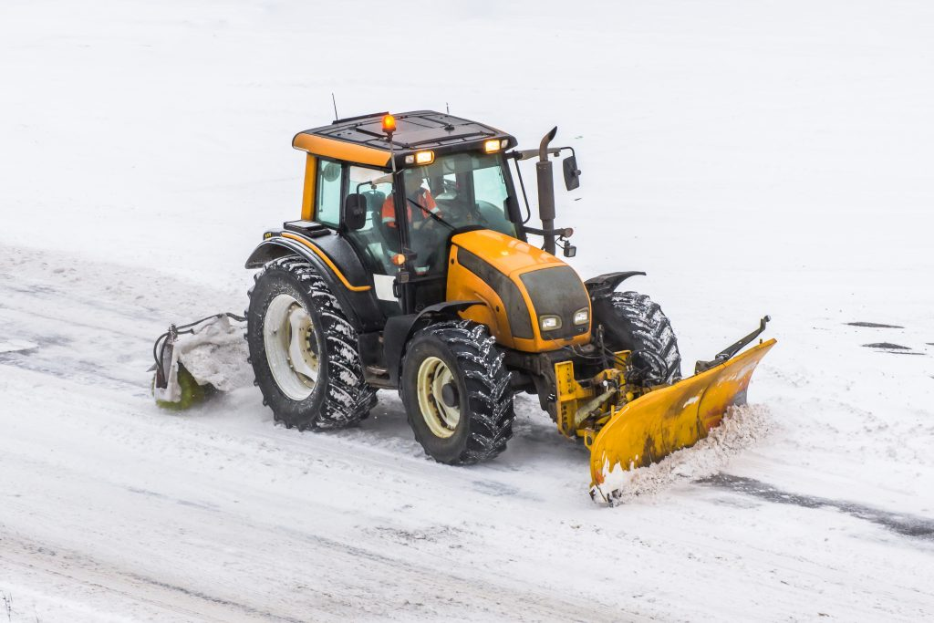 Large snow plowing tractor machine at work on the road during a snow storm in winter.